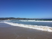 The Pacific Ocean tranquilly laps at the beach with the city of Monterey in the background.