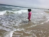 My sister enjoys the feel of the cool, pacific waves.